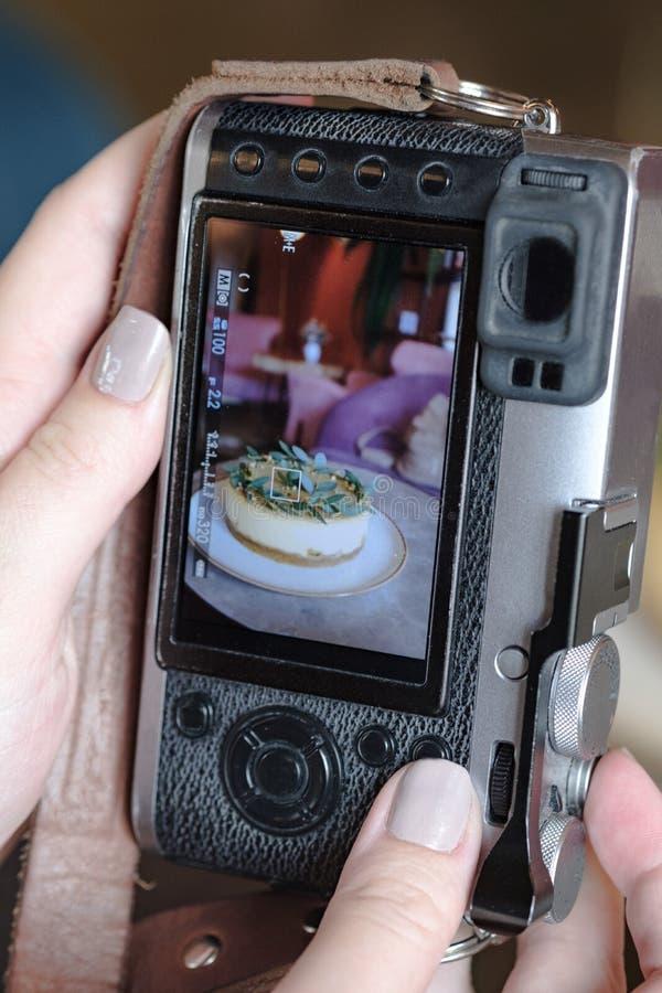 Een vrouw neemt een foto van de cake gebruikend een mirrorless camera royalty-vrije stock afbeelding