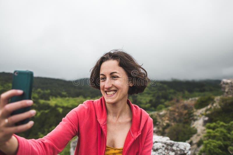 Een vrouw neemt een selfie bovenop een berg royalty-vrije stock afbeeldingen