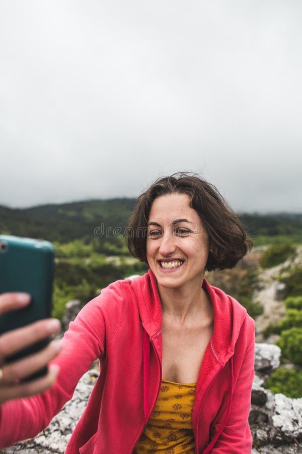 Een vrouw neemt een selfie bovenop een berg royalty-vrije stock afbeelding