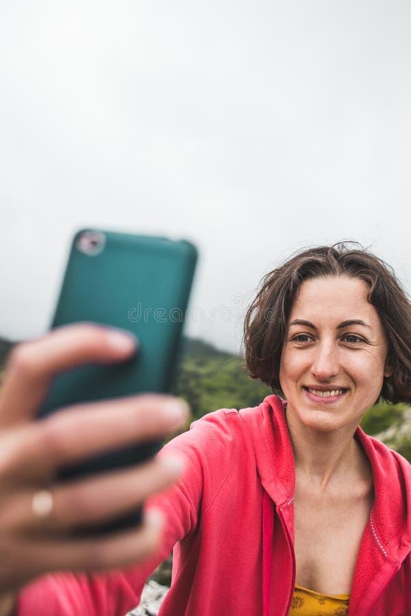 Een vrouw neemt een selfie bovenop een berg royalty-vrije stock foto's
