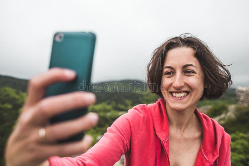 Een vrouw neemt een selfie bovenop een berg royalty-vrije stock foto