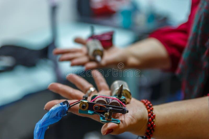 Een vrouw neemt twee tatoegeringsmachines in haar handen royalty-vrije stock foto's