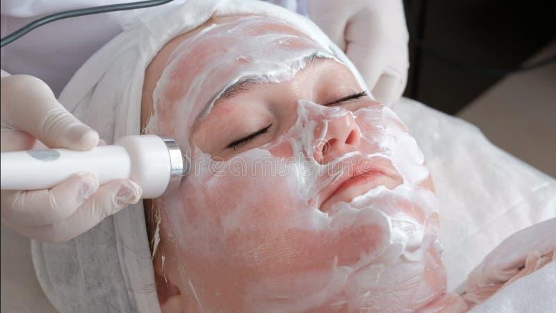 Een vrouw ondergaat phonophoresis van huid het opheffen De schoonheidsspecialist zette punten op het gezicht met behulp van een w royalty-vrije stock foto