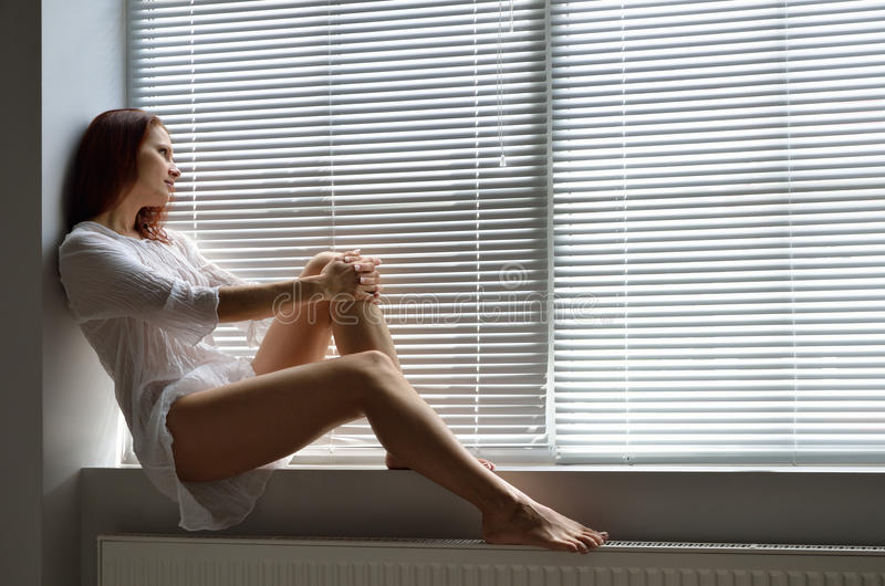 Een vrouw op de vensterbank thuis stock foto