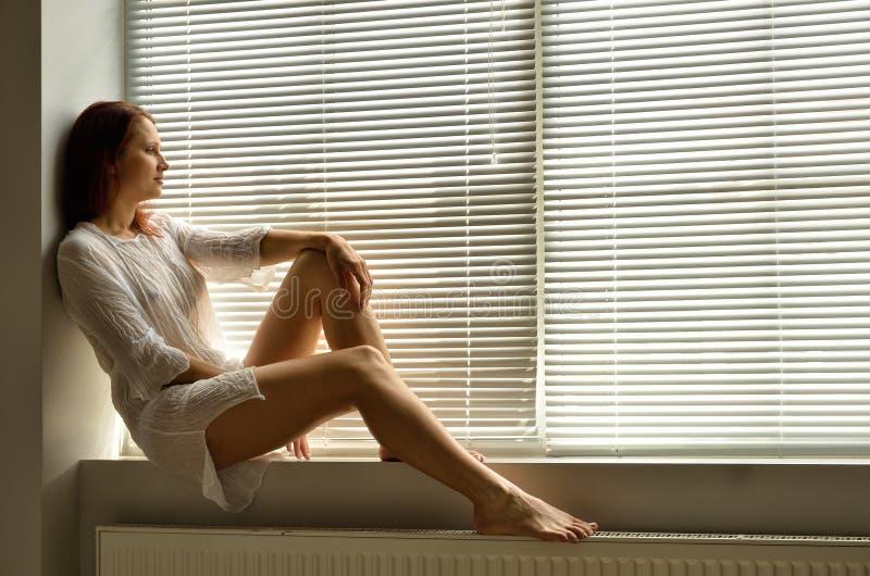 Een vrouw op de vensterbank thuis royalty-vrije stock fotografie