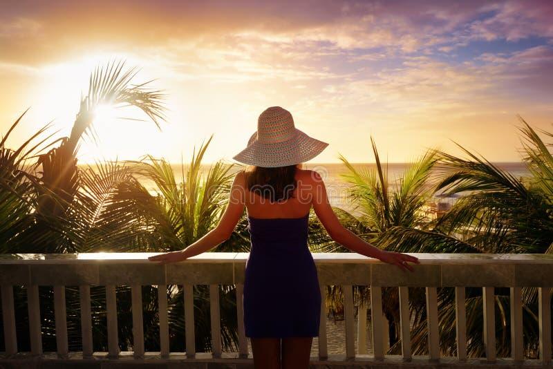 Een vrouw op een balkon die de mooie Caraïbische zonsondergang bekijken stock afbeelding