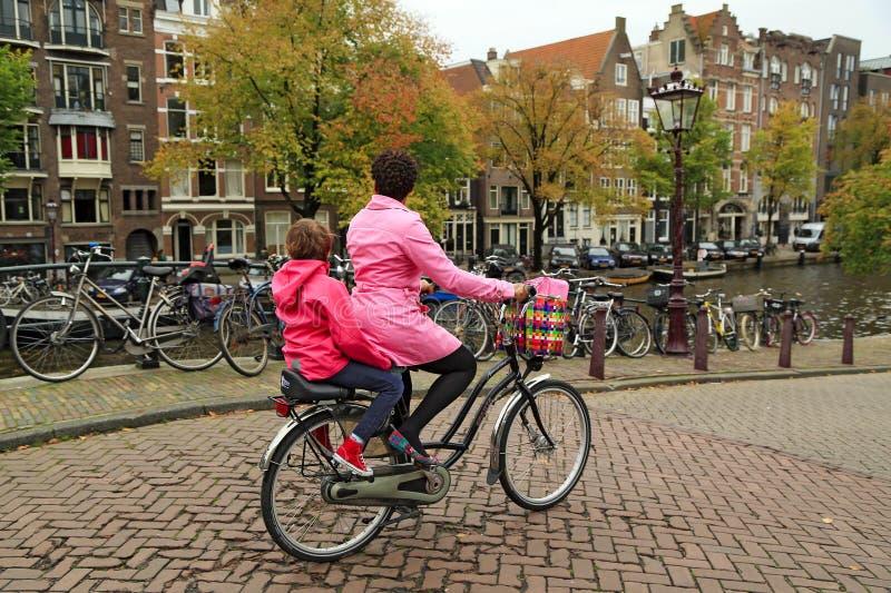Een vrouw op een fiets, die haar kind op de achterkindzetel vervoeren Amsterdam, Nederland royalty-vrije stock fotografie