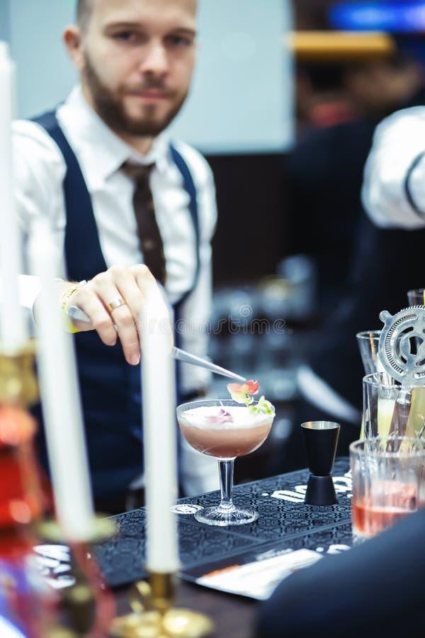 Een vrouw past een olievlek van lipgloss op haar lippen toe De barman voegt bloembloemblaadjes aan de cocktail toe stock afbeeldingen