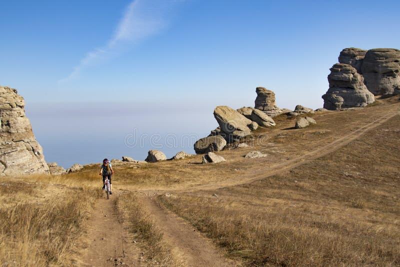 Een vrouw rijdt op fietsachtergrond van bergen en een blauwe lucht stock foto