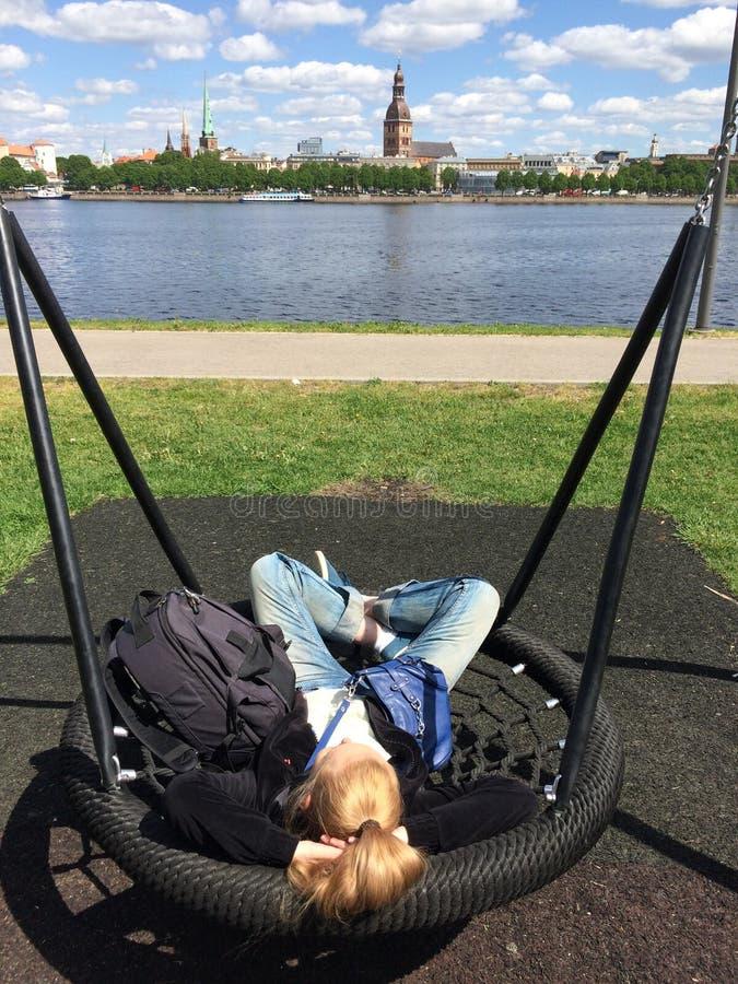 Een vrouw rust in een park op een schommeling die de Daugava-Rivier en de oude stad van Riga aan de andere kant overzien stock foto's
