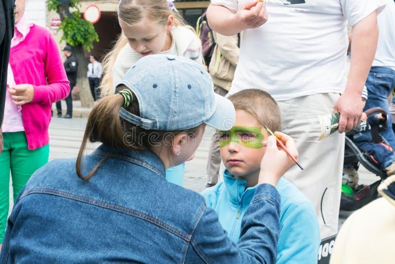 een vrouw schildert het jongens` s gezicht met kleuren, tijdens de viering van de Dag van Europa royalty-vrije stock afbeeldingen