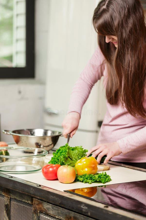 Een vrouw snijdt een komkommer en groenten met een mes Het jonge Vrouw Koken in de keuken thuis Gezond voedsel Dieet stock afbeelding