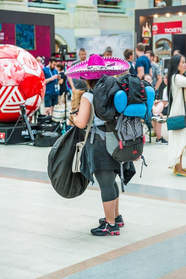 Een vrouw in een sombrero met een grote rugzak en zakken stock afbeeldingen