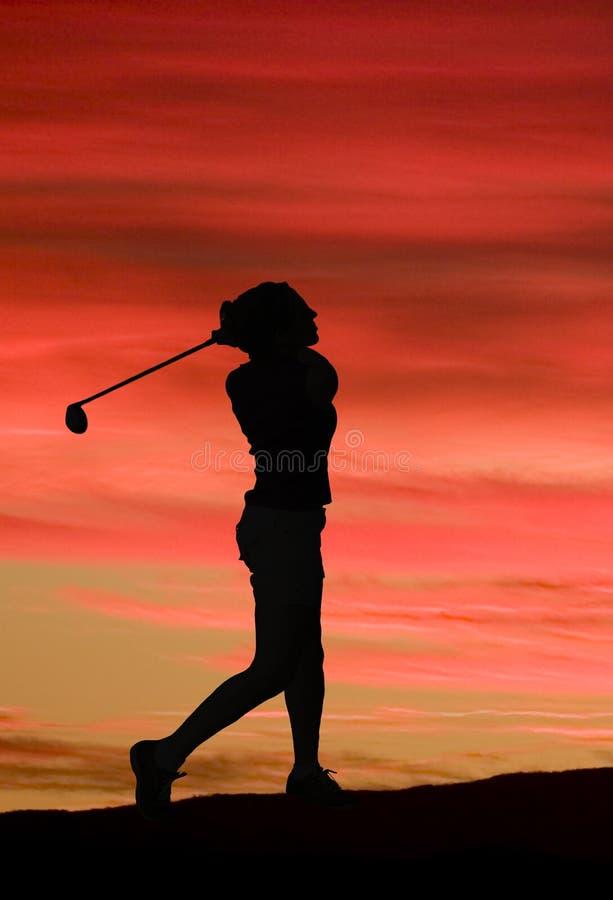 Een vrouw speelt golf tegen een briljante zonsondergang stock afbeeldingen