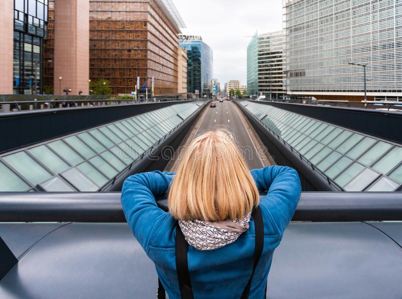 Een vrouw staat op een brug met haar rug naar de camera tegen de achtergrond van een moderne kantoorruimte, België royalty-vrije stock afbeeldingen