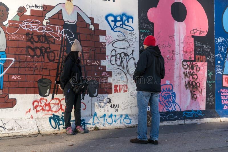Een vrouw stelt voor een foto bij de Zijgalerij van het Oosten, Berlijn stock afbeelding