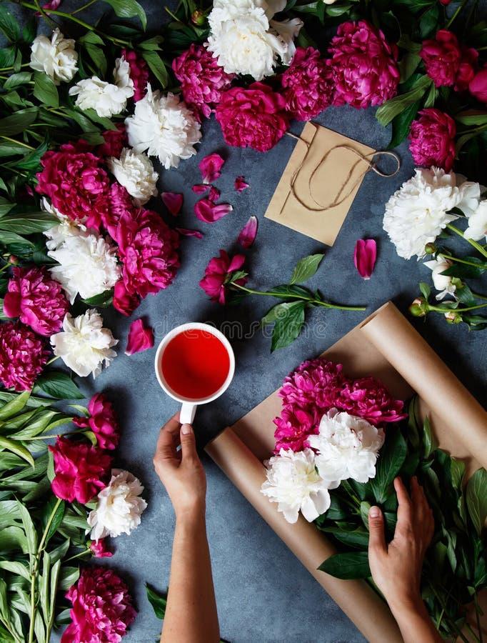 Een vrouw tijdens het maken van een de zomerboeket van pioenen, houdt in haar hand een kop thee karkade Hulpmiddelen en royalty-vrije stock fotografie