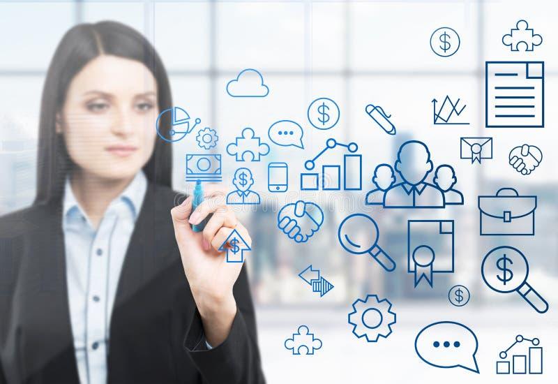 Een vrouw trekt sommige bedrijfspictogrammen op het glasscherm Modern panoramisch bureau met de mening van New York in onduidelij stock afbeelding