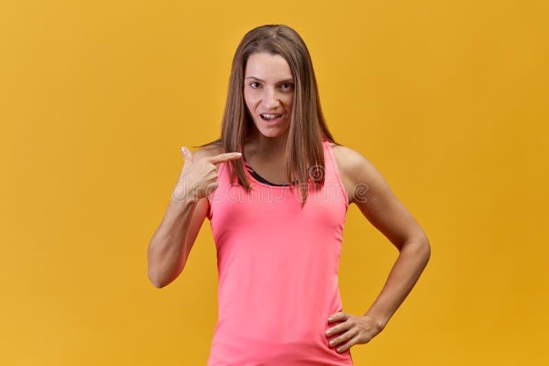 Een vrouw van de blondeatleet bekijkt expressively camera en toont haar vinger bij zich op een geïsoleerde oranje achtergrond stock foto