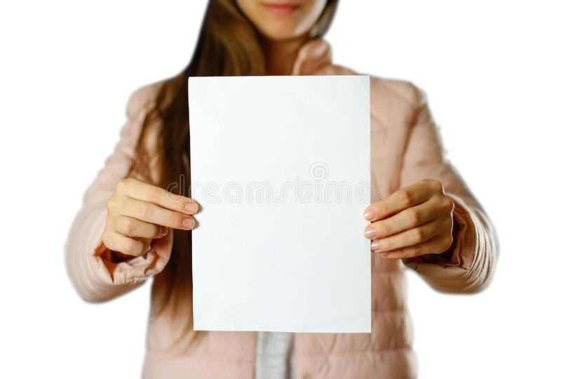 Een vrouw in een warm de winterjasje die een wit pamflet houden Leeg document Sluit omhoog Geïsoleerdj op witte achtergrond stock fotografie