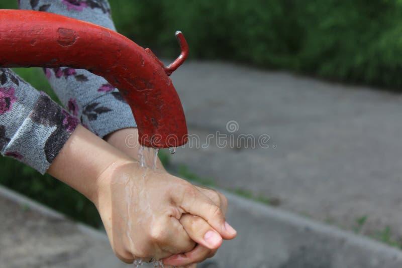 Een vrouw wast haar handen De oude pomp van de waterhand in het centrum van de moderne stad royalty-vrije stock foto