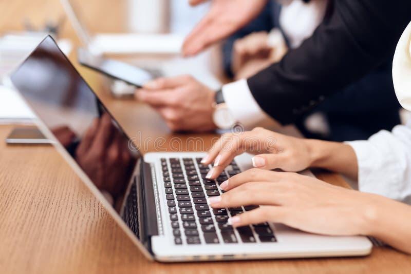 Een vrouw werkt aan laptop Het drukt op het toetsenbord stock afbeelding