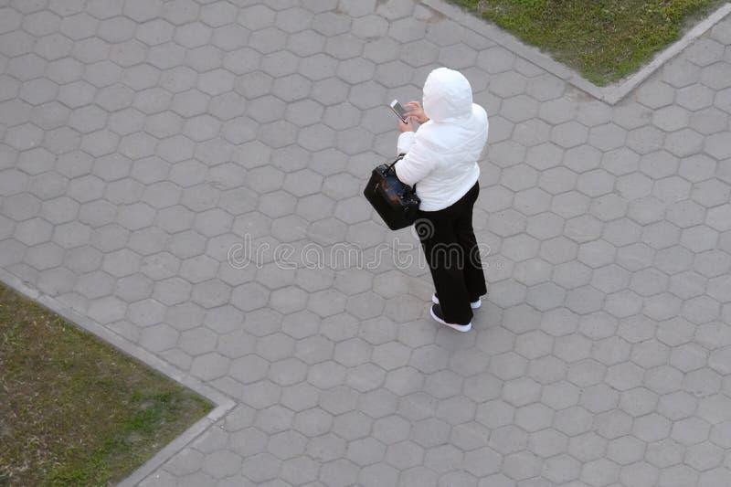 Een vrouw in een wit jasje en een zwarte broek houdt een zak en een telefoon in haar hand Mening van hierboven, straat, weg als p royalty-vrije stock foto