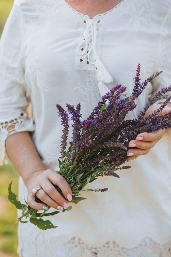 Een vrouw in een witte blouse met een mooie manicure houdt een boeket van wildflowerssalie in haar handen stock fotografie