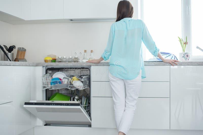 Een vrouw in witte jeans en een turkoois overhemd bevindt zich met haar terug naast een open afwasmachine in een wit keukenbinnen stock foto