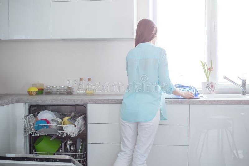 Een vrouw in witte jeans en een turkoois overhemd bevindt zich met haar terug naast een open afwasmachine in een wit keukenbinnen royalty-vrije stock afbeeldingen