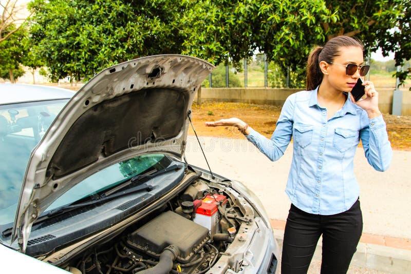 Een vrouw wordt geplakt met een gebroken auto, vereist hulp, motiveert de auto niet royalty-vrije stock afbeeldingen