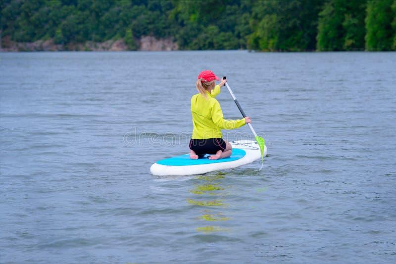 Een vrouw zit aan boord van en bekijkt de horizon Reis en het concept wateractiviteit Lege ruimte en waterachtergrond royalty-vrije stock foto