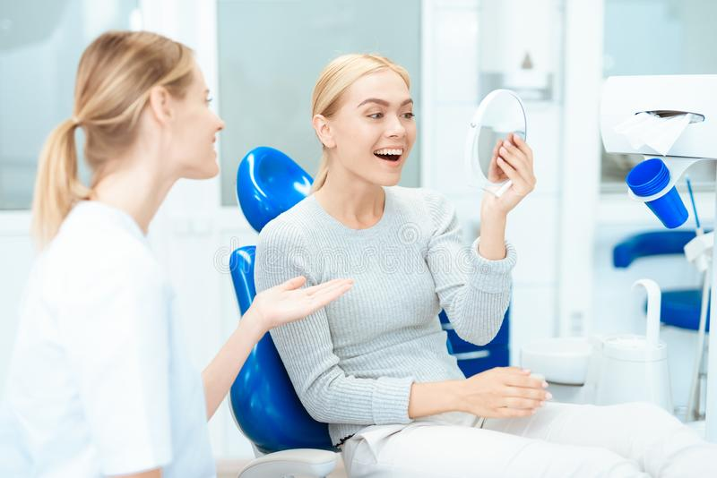 Een vrouw zit bij een tandarts` s ontvangst Zij bekijkt in de spiegel haar tanden Vrouw het glimlachen royalty-vrije stock foto's