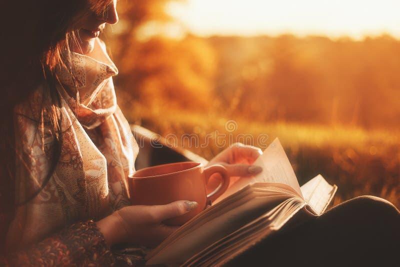 Een vrouw zit dichtbij een boom in een de herfstpark en houdt een boek en een kop met een hete drank in haar handen Meisje dat ee royalty-vrije stock foto's