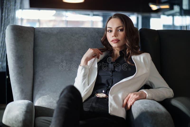 Een vrouw zit in een koffie Close-up, die weg eruit zien royalty-vrije stock afbeelding