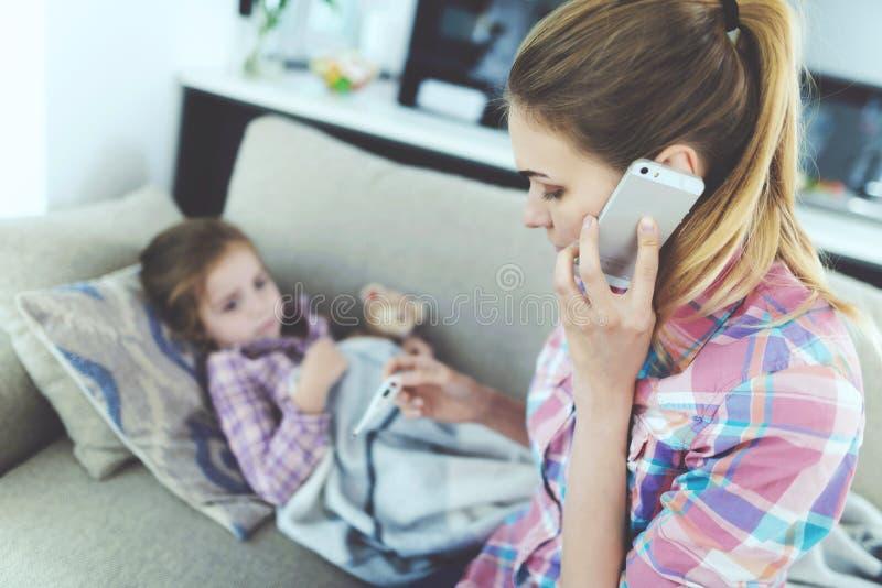Een vrouw zit naast een klein meisje dat ziek is Zij houdt een thermometer, die de meisjes` s temperatuur mat stock foto's