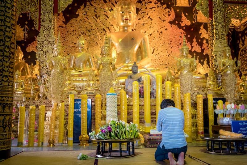 Een vrouw zit om voor het gouden standbeeld van Boedha van Thailand tempel genoemd 'Wat Den Salee Sri Muang Gan Wat Ban Den 'te b stock afbeeldingen