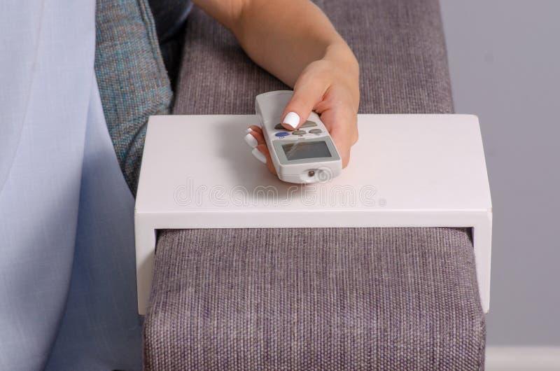 Een vrouw zit op de laag in de handen van een afstandsbediening van een airconditioner stock afbeeldingen