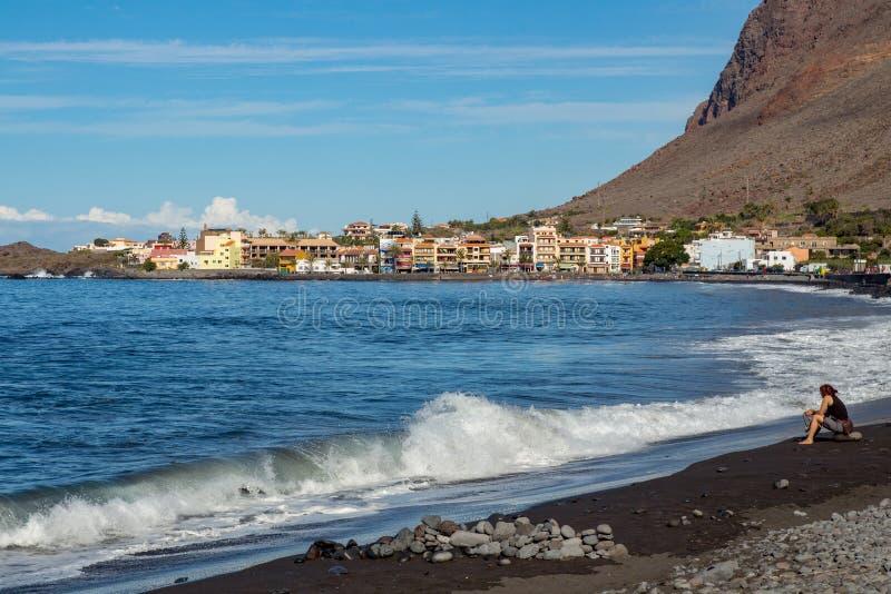 Een vrouw zit op het strand van Valle Gran Rey royalty-vrije stock afbeelding