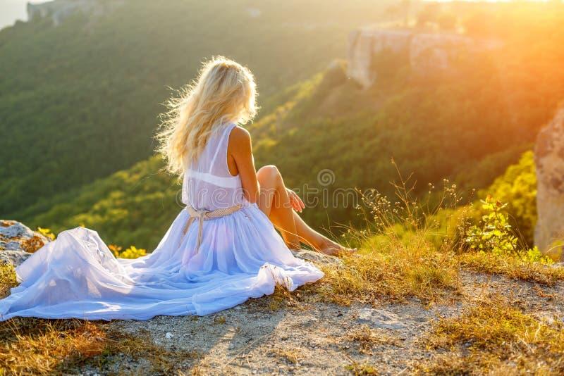Een vrouw zit op een rots en bekijkt de mooie mening in de zon royalty-vrije stock afbeeldingen