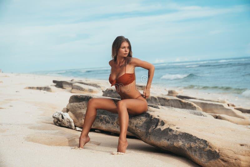 Een vrouwelijk model in een sexy rood zwempak in een ondiep wit punt maakt een gelijke tegen de achtergrond van een zandig strand stock afbeelding