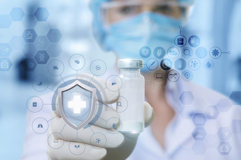 Een vrouwelijke arts in het medische masker toont een vaccin in haar rubberhandschoen indient stock foto