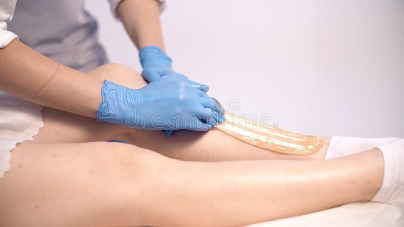 Een vrouwelijke artsenschoonheidsspecialist past suikerdeeg op de huid van de cliënt` s benen toe stock foto's