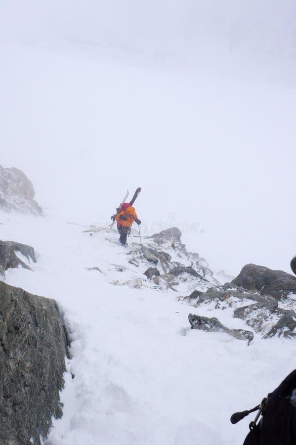 Een vrouwelijke backcountry skiër die omhoog op een hoge alpiene berg in de Oostenrijkse Alpen in de winter in slecht weer wandel stock fotografie