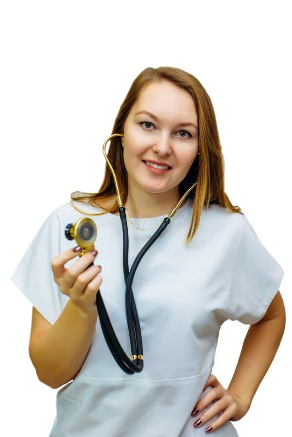 Een vrouwelijke die arts met een stethoscoop op witte achtergrond wordt geïsoleerd Glimlachende artsenvrouw met in hand stethosco stock foto