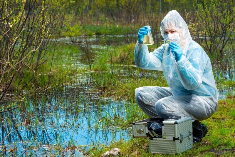 een vrouwelijke ecologist met steekproeven van water en flora van een meer royalty-vrije stock foto's
