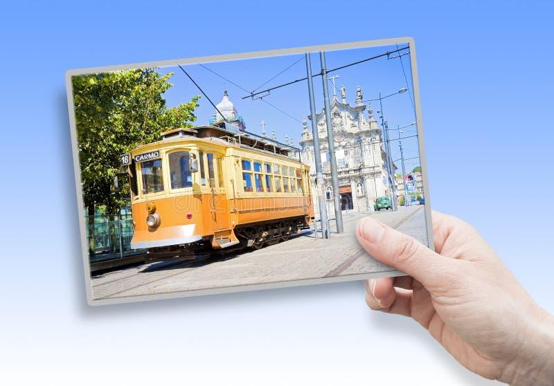 Een vrouwelijke hand die een prentbriefkaar over historische trasportation van Porto - op achtergrond 'houden Igreja do Carmo e C stock afbeelding