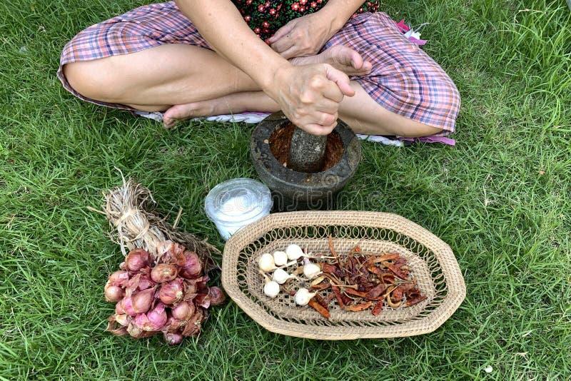 Een vrouwelijke hand die vele soorten kruiden in mortier verpletteren om het Thaise rode deeg van de kerriespaanse peper te maken stock foto