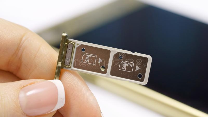 een vrouwelijke hand houdt een dubbele SIM-kaartgroef stock foto