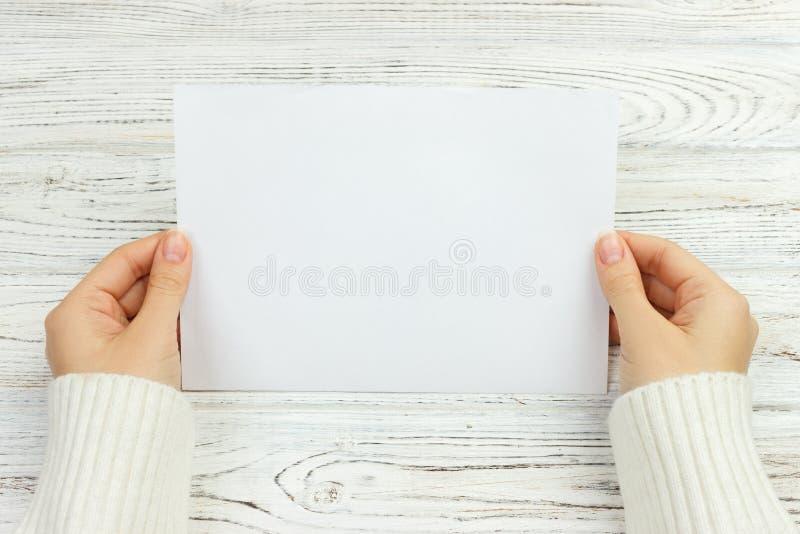 Een vrouwelijke hand houdt een envelop en een prentbriefkaar op het houten bureau, de hoogste ruimte van het meningsexemplaar stock foto's